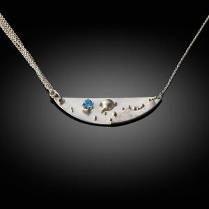 'Night at sea'. Mokume gane pendant (silver/white gold) with blue topaz
